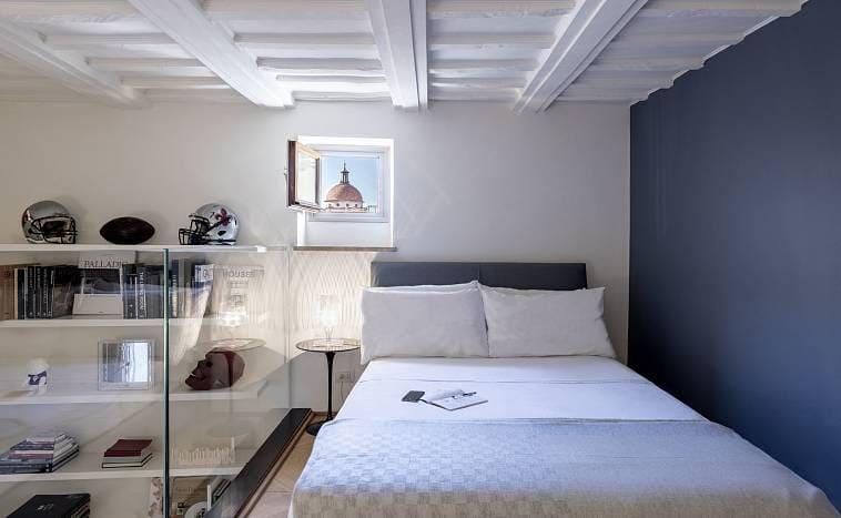 Спальня с кроватью у стены и с широкими полками