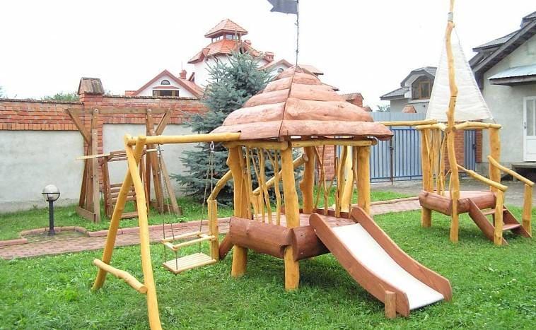 Детская площадка с домиком из бревен